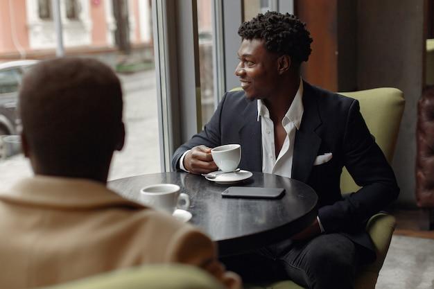 Czarni mężczyźni siedzą w kawiarni i piją kawę