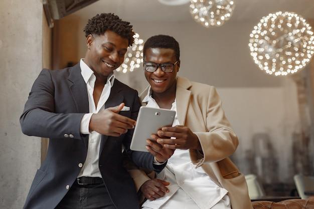 Czarni mężczyźni w kawiarni mają interesy