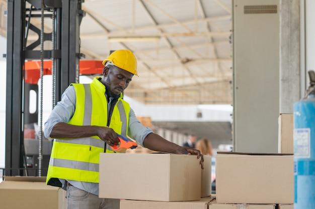 Czarni pracownicy płci męskiej noszą żółty kask ochronny, pakując ładunek do pudeł, aby przygotować się do wysyłki w fabryce magazynowej.
