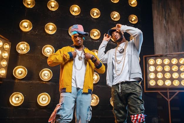 Czarni raperzy w czapkach na scenie z reflektorami