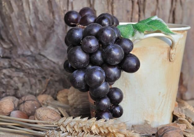 Czarni winogrona w dekoracyjnym wiadrze na nieociosanym drewnianym tle
