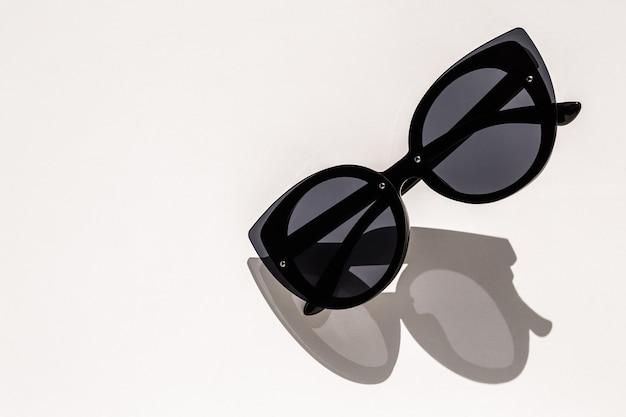 Czarni żeńscy okulary przeciwsłoneczni na bielu w świetle słonecznym