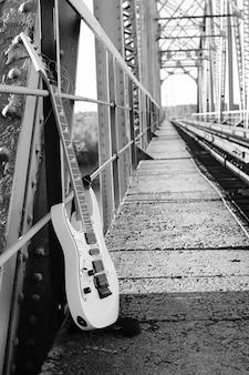 Czarno-biała gitara elektryczna na torach kolejowych i industrialny szary kamień
