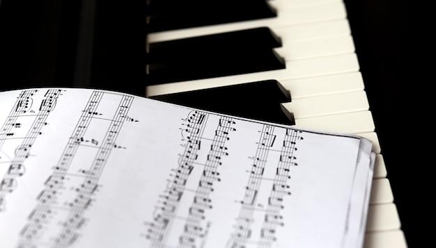 Czarno-biała klawiatura fortepianowa z nutami. pojęcia takie jak muzyka i kreatywność.