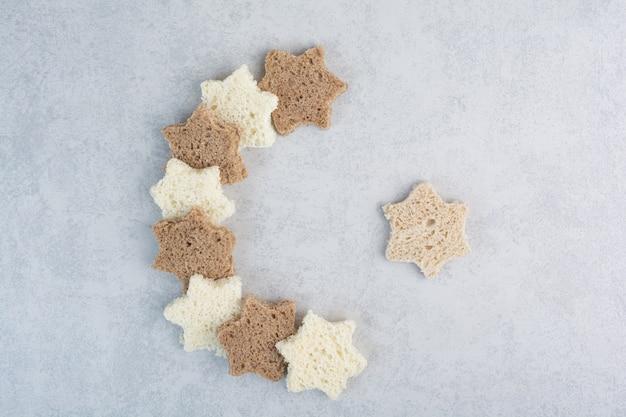 Czarno-białe kromki chleba w kształcie gwiazdy na tle marmuru. wysokiej jakości zdjęcie