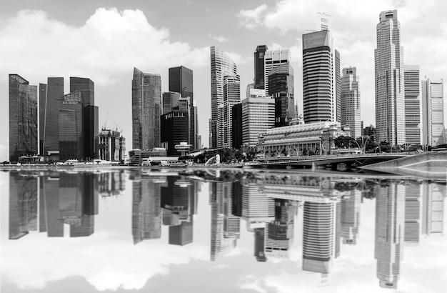 Czarno-białe obrazy drapaczy chmur i odbicia w mieście.