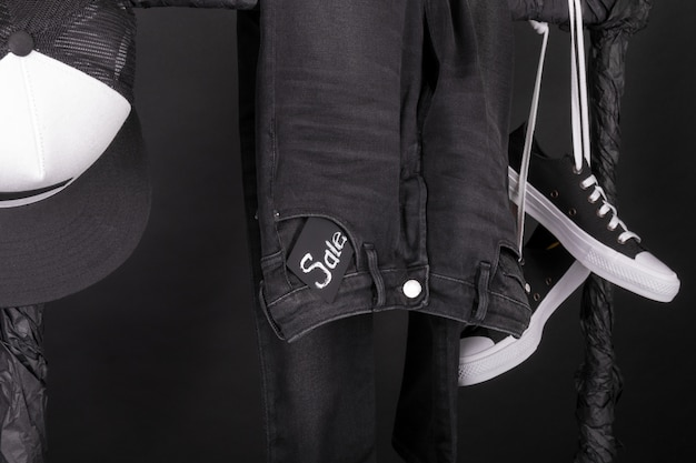 Czarno-białe snaekery, czapka i spodnie, dżinsy wiszące na wieszaku na ubrania.