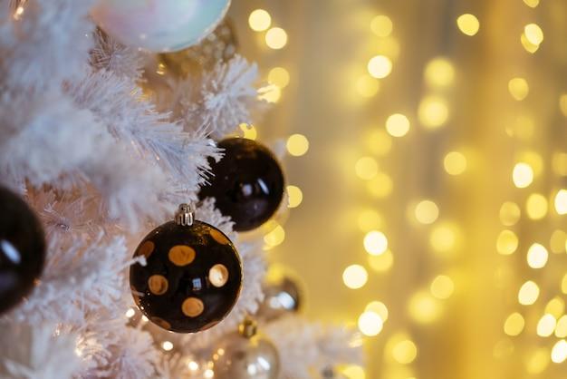 Czarno-białe zabawki na zbliżeniu noworocznej choinki miejskiej świecąca biała choinka ...
