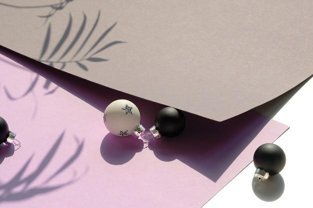 Czarno-białe zabawki świąteczne na warstwowym papierze z cieniami liści palmowych