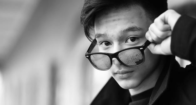 Czarno-białe zdjęcie azjatyckiego młodego mężczyzny na zewnątrz pozującego przed kamerą