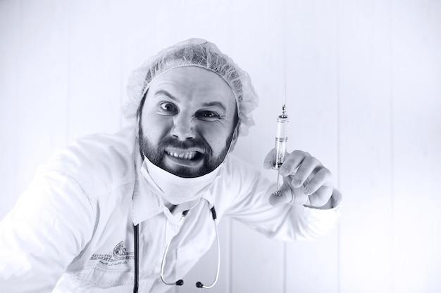 Czarno-białe zdjęcie brodatego lekarza w białym fartuchu i starej strzykawce