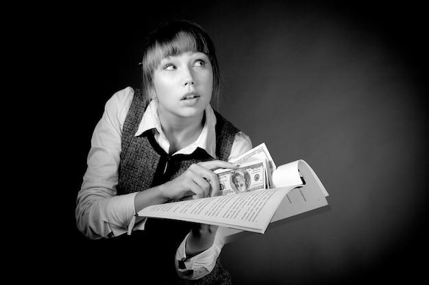 Czarno-białe zdjęcie dość przebiegłej młodej kobiety próbującej dać łapówkę