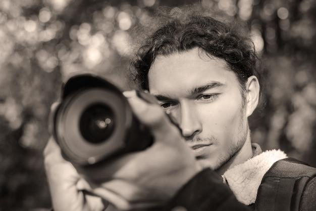 Czarno-białe zdjęcie fotografa strzelającego do kogoś w parku. robienie zdjęć w parku