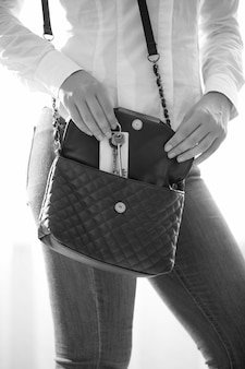 Czarno-białe zdjęcie kobiety z małą torebką trzymającą klucze do domu