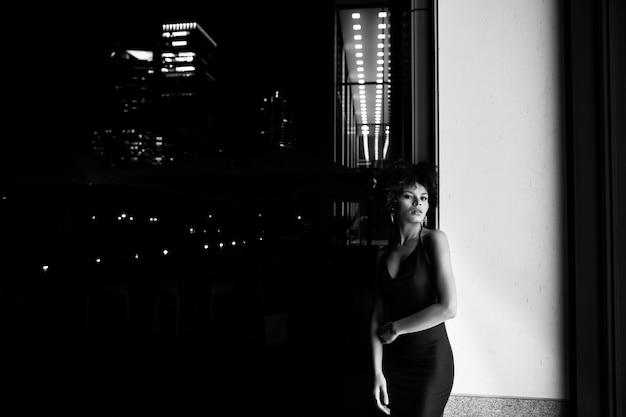Czarno-białe zdjęcie młodej kobiety afroamerykanów w nocy. kobieta pozuje blisko iluminującego okno na ulicie i patrzeje w kamerę. koncepcja życia nocnego, mody i stylu