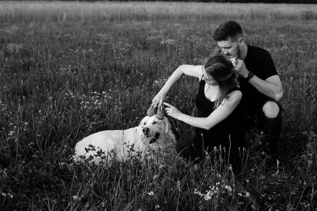 Czarno-białe zdjęcie młodej pary w ciąży, która oddaje się spacerowi z psem, kładąc na głowę dziecięce buty. beztroski i szczęśliwy. czekam na dziecko. ciąża. szczęśliwe momenty.