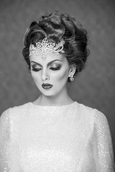 Czarno-białe zdjęcie nowoczesnej panny młodej z fryzurą i makijażem ślubnym, ubrana w suknię ślubną