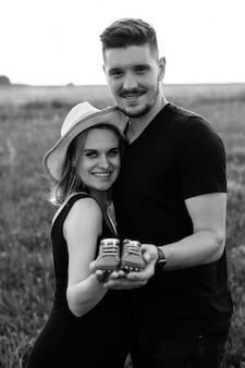 Czarno-białe zdjęcie pięknej młodej pary w ciąży szczęśliwy czeka na dziecko i trzyma buty dla dzieci. beztroski i szczęśliwy. spacery z całą rodziną. ciąża i opieka. szczęśliwe momenty.