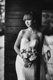 Czarno-białe zdjęcie. portret panny młodej w białej sukni z bukietem w ręku z bliska. panna młoda. piękno portret panny młodej jest ubranym modną ślubną suknię z luksusowym zachwyta makijażem i fryzurą. ślub.