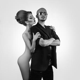 Czarno-białe zdjęcie poważnego silnego mężczyzny z gorącą nagą kobietą