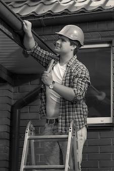 Czarno-białe zdjęcie pracownika naprawiającego dach i rynnę