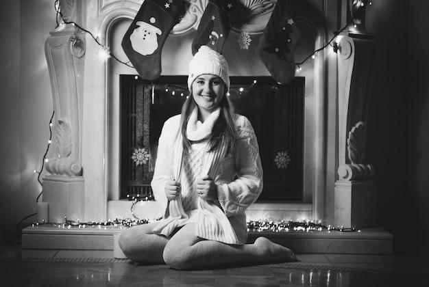 Czarno-białe zdjęcie uśmiechniętej kobiety siedzącej na podłodze przy kominku
