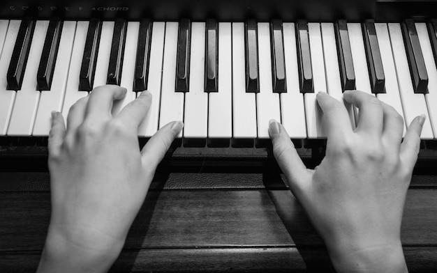 Czarno-białe zdjęcie z bliska kobiecych rąk grających na pianinie