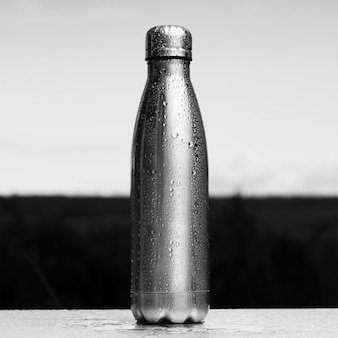 Czarno-białe zdjęcie, zbliżenie butelki termo spryskane wodą.