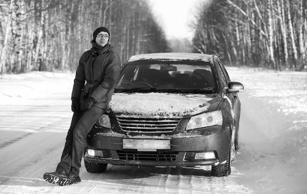 Czarno-białe zdjęcie zimowej wiejskiej drogi w lesie w słoneczny dzień i mężczyzna z samochodem