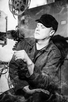 Czarno-białe zdjęcie zmęczonego kamerzysty palącego w sali kinowej.
