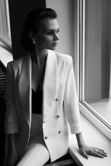 Czarno-biały modny portret pięknej luksusowej kobiety w białej kurtce, profesjonalnym makijażu i efektownych dodatkach