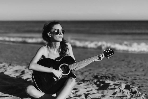 Czarno-biały obraz dziewczyny gra na gitarze na plaży