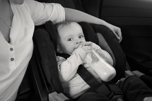 Czarno-biały obraz matki karmiącej dziecko z butelki w samochodzie