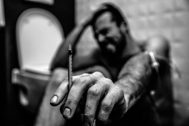 Czarno-biały obraz młodego człowieka w toalecie siedzieć i cierpieć. pokazuje cienką strzykawkę w ręku na aparacie. facet krzyczy i kurczy się. blade słabe ciało
