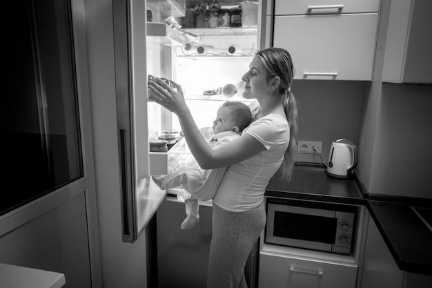 Czarno-biały obraz młodej matki i synka zaglądających do lodówki w poszukiwaniu czegoś do jedzenia