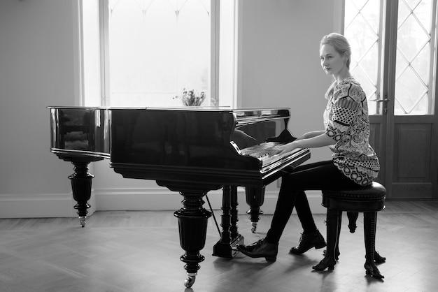 Czarno-biały obraz pianistka grająca fortepiano przed oknem koncepcja równości kobiet