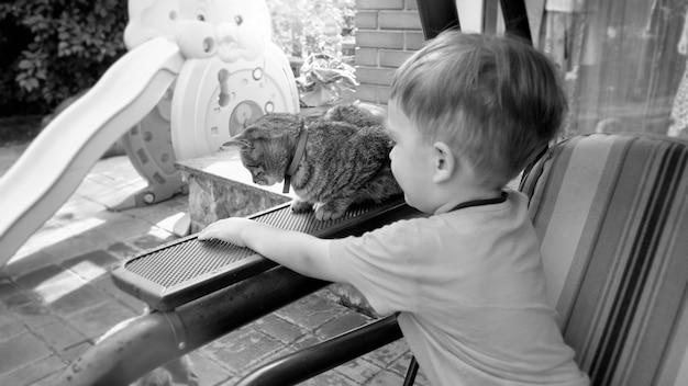 Czarno-biały obraz uroczego małego chłopca siedzącego na ławce w ogrodzie przydomowym domu i pieszczącego kota