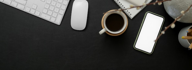 Czarno-biały obszar roboczy ze smartfonem, urządzeniem komputerowym, filiżanką kawy, notatnikiem i kopią
