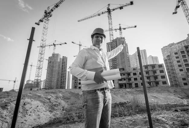 Czarno-biały portret architekta pozowanie na placu budowy z planami