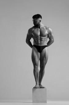 Czarno-biały portret atletycznego szczupłego mężczyzny stojącego w pełnym wzroście na sześcianie