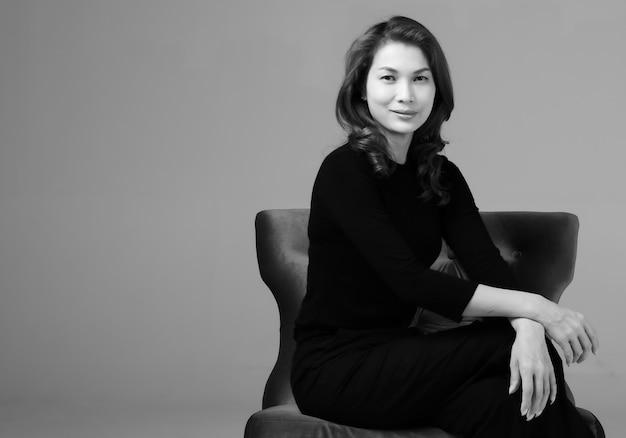 Czarno-biały portret azjatyckie kobiety siedzącej na krześle i patrząc na kamery z siebie i miejsca kopiowania.