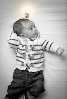 Czarno-biały portret inteligentnego chłopca ze świecącą żarówką nad głową