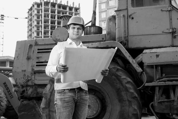 Czarno-biały portret inżyniera czytającego instrukcje buldożerowi