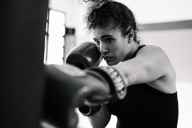 Czarno-biały portret kobiety bokser rękawice treningowe na siłowni