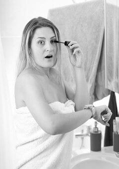 Czarno-biały portret kobiety stosującej tusz do rzęs w łazience i patrzący na zegarek