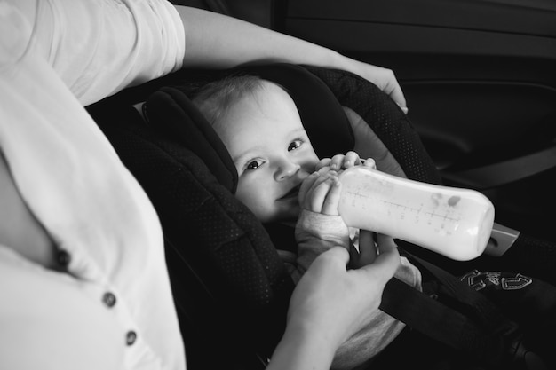 Czarno-biały portret matki karmiącej dziecko z butelki w samochodzie