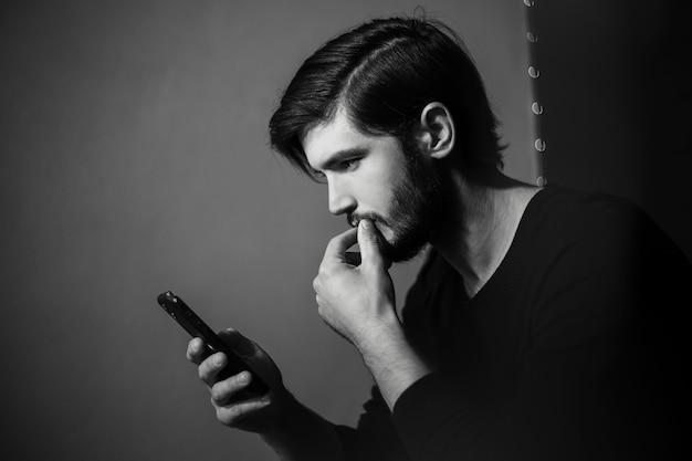 Czarno-biały portret młodego człowieka z smartphone w ręku.