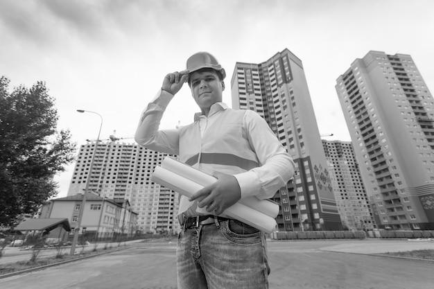 Czarno-biały portret młodego inżyniera uśmiechniętego stojącego na placu budowy