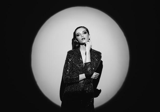 Czarno-biały portret modnej dziewczyny z włosami ściągniętymi do tyłu i stylowym makijażem w lśniącej sukience stojącej przy ścianie w jasnym świetle reflektorów.