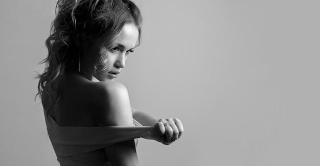 Czarno-biały portret niesamowitej młodej kobiety z kręconymi włosami i gołymi ramionami. miejsce na tekst